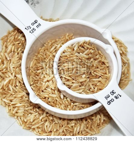 Uncooked whole grain brown rice in two different sized measuring cups