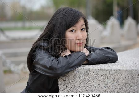 Portrait of asian woman in black jacket at park