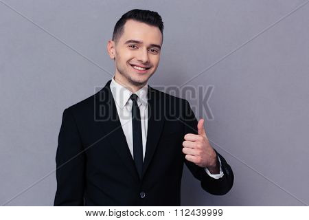 Portrait of a smiling businessman showing thumb up over gray background