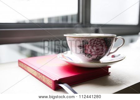 Steamy Tea Cup, Placed On Top Of A Book