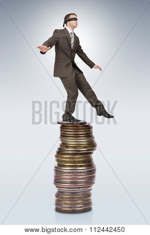 Businessman walking from edge of coins pile