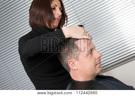 Female Hairdresser Cutting Hair Of Smiling Man Client At Beauty Parlour