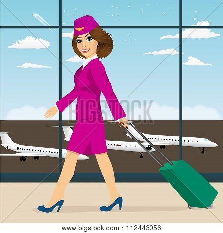 stewardess with luggage walking through airport terminal