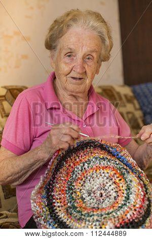 An elderly woman knits crochet rug.