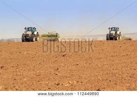 View Of Two Tractors Sowing In Field In Spring
