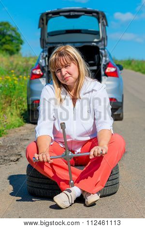 Female 50 Years Sitting On A Spare Wheel Near The Car On The Road