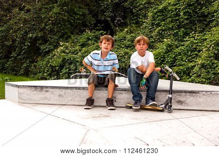Boys Are Sitting At A Box In The Skate Park And Relaxing From Skating And Scooting