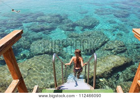 She Descends Into The Clear Water Of The Mediterranean Sea
