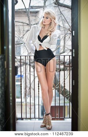 Beautiful young woman with long legs in black lingerie and white male shirt posing outdoor