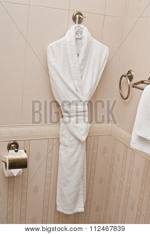 White fresh bath robe hang on bathroom wall. White shower gown and small towels hang in the bathroom