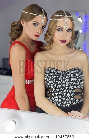 two beautiful sexy elegant girl in a red and black evening dresses with bright evening make-up eveni