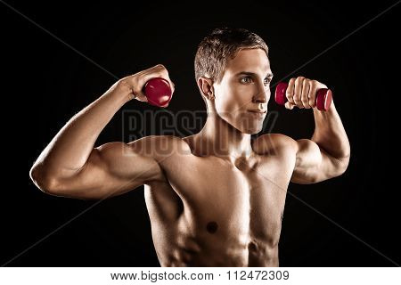 Young handsome well formed sporty man on black background. Fit sportsman exercising with red dumbbells
