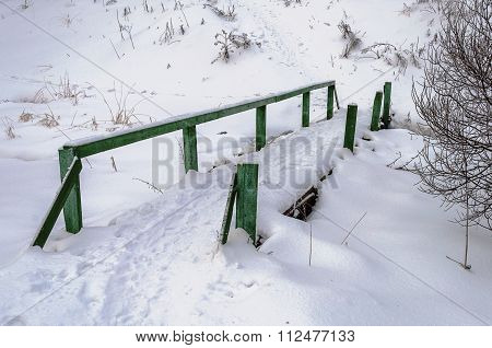Old Wooden Footbridge Covered With Snow In The Village