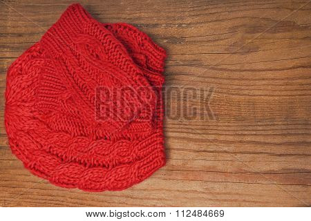 Red knitted cap and mittens on a wooden background.
