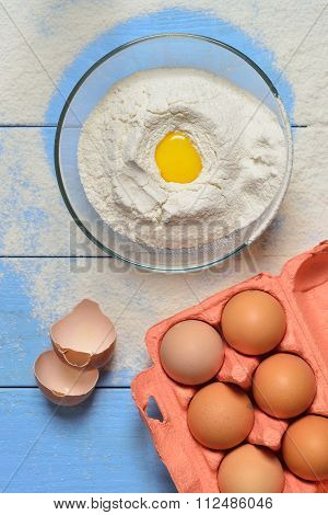 Glass Bowl With Flour On A Blue Wooden Background, Eggshells And Egg Yolk In The Flour Box With Eggs