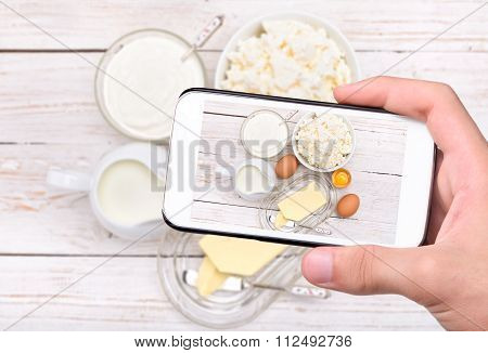 Hands taking photo dairy products with smartphone.