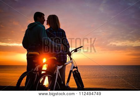 Couple of cyclists at the beach at sunset.