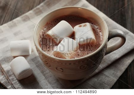 Cup of hot cacao with marshmallow on cotton serviette, close up