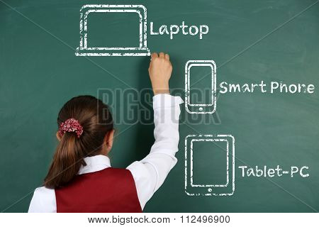 Little girl drawing different gadgets on the chalkboard