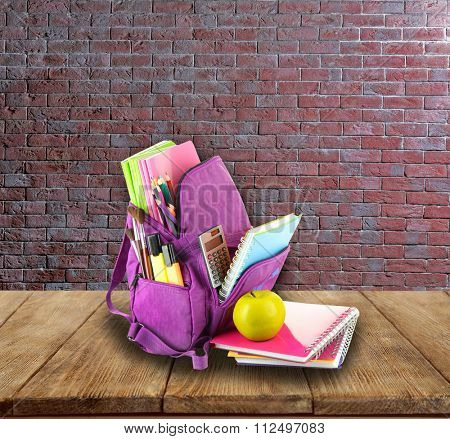 School backpack on wooden desk, on bricks wall background