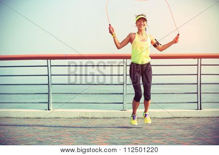 one young woman jumping rope on seaside