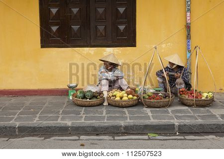 Fruits vendors selling agricultural products on a street of Hoi An ancient town