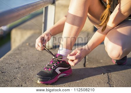 Girl tying shoelaces on sneakers. Close-up.