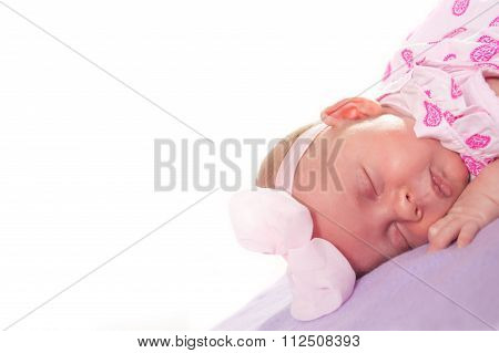 Newborn baby girl slipping on her tummy