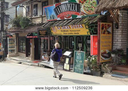 Visitor walking on a street with many restaurants in Sapa tourism town