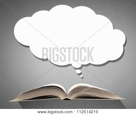 Opened book with speech cloud above pages