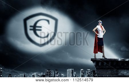 Young woman super hero and euro sign in spotlight