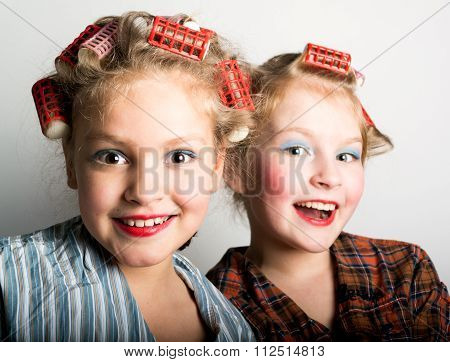 Two playful teenage girls in front of one eye laughing happily at the camera as they stand side by s