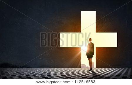 Businesswoman standing with back in light of cross door