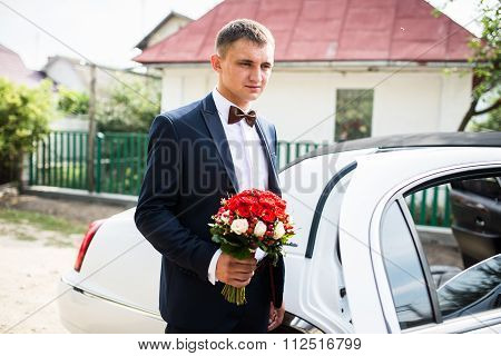 Groom Stay With Bouquet Near Limousine