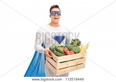 Young man in superhero costume carrying a wooden crate full of fresh vegetables isolated on white background
