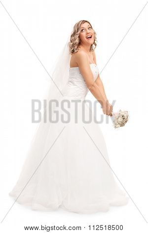 Full length portrait of a young blond bride tossing her wedding bouquet isolated on white background