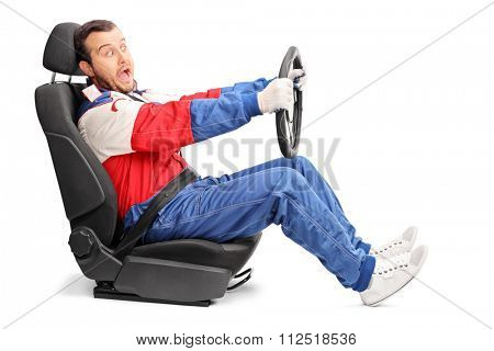 Studio shot of a young car racer pretending to drive very fast seated on a car seat isolated on white background