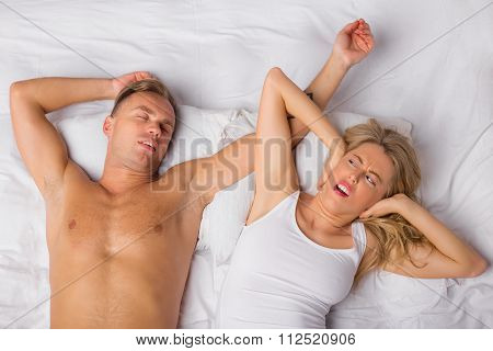 Woman holding her ears because of man snoring