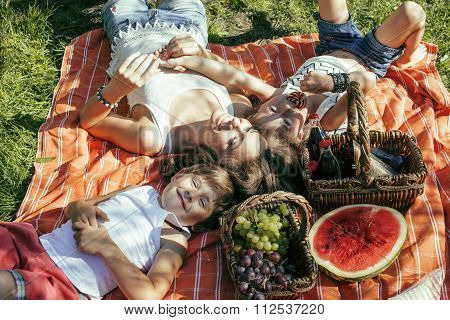 cute happy family on picnic laying on green grass mother and kids, warm summer vacations close up