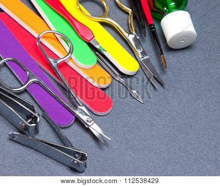 Various Manicure Tools On Gray Textured Background