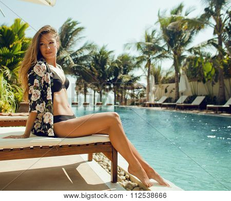 young pretty woman at swimming pool relaxing in chair, fashion look lingerie at hotel close up smili