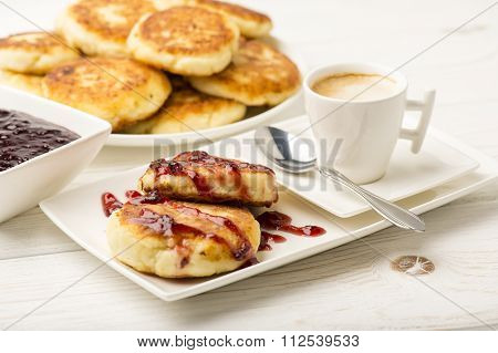 Cottage cheese pancakes with a cup of coffee on the white wooden background.