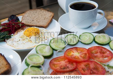 Coffee cup, scrambled eggs and salad breakfast on table