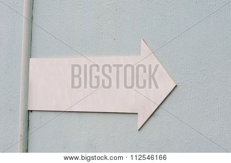 Pink Elongated Arrow On Rough Bluish Background With Vertical Tube