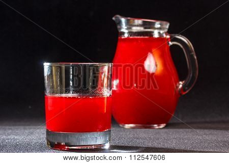 Red drink poured into a glass in the background is worth a pitcher of the same drink.