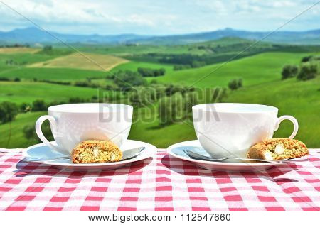 Coffee and cantuccini on the table against Tuscan landscape. Italy
