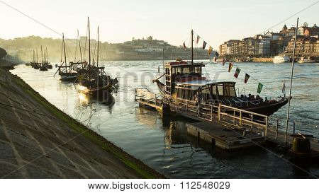 PORTO, PORTUGAL - CIRCA JUN, 2015: Ribeira, traditional boats at Douro river in Old Town, Luiz iron bridge in background. In 1996, UNESCO recognised Old Town of Porto as a World Heritage Site.