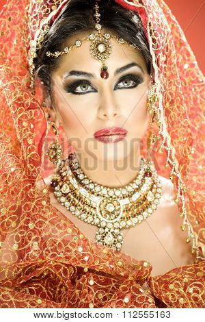 Portrait of a beautiful female model in traditional indian bride outfit with jewellery and makeup
