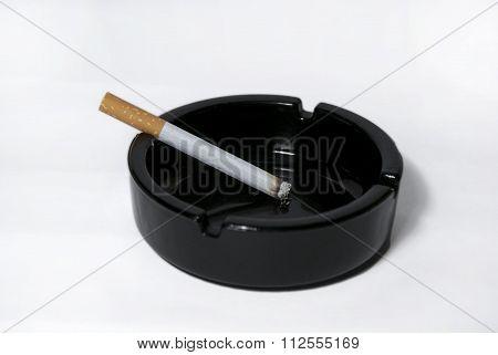 Black ashtray and cigarette over white background