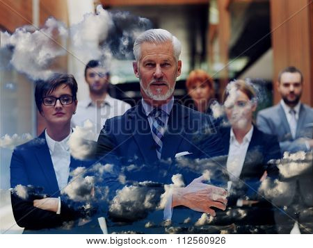 double exposure of senior businessman with his team at office. multi exposure of business people group and clouds and mountains nature